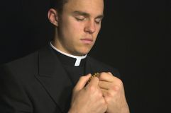 Young Priest praying. With rosery in his hands Stock Photos
