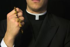 Young Priest praying with rosary Royalty Free Stock Image
