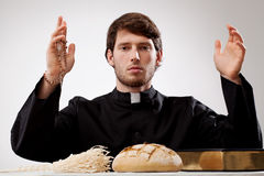 Young priest. With rosary bread sprinkler and Holy Bible Stock Images