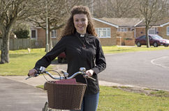 Young priest using a bicycle to visit her parish Royalty Free Stock Photography