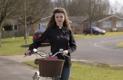 Young priest using a bicycle to visit her parish Stock Images