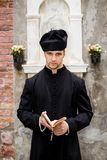 Young priest in venice. With church Stock Photo
