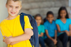 Young primary schoolboy. Cute young primary schoolboy with arms crossed in front of classmates royalty free stock photo