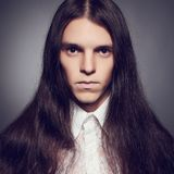 Young prince concept. Old fashioned portrait of gothic man. Old fashioned portrait of a long-haired young man in white vintage shirt posing over dark gray stock image