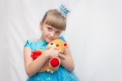 The young Princess in a blue dress and crown, on a white background and is holding a Teddy bear. Portrait of a child. Royalty Free Stock Images