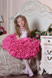 Young princess in an elegant pink dress sitting. On a bed Royalty Free Stock Photography