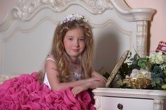 Young princess in an elegant pink dress sitting Stock Photos
