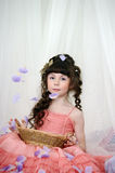 Young princess with pink dress with rose petals. And a basket Royalty Free Stock Images