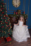 Young princess in a white dress with a tiara on her head at the Christmas tree Stock Photography