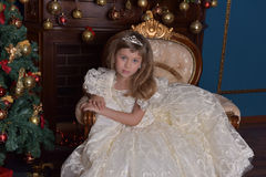 Young princess in a white dress with a tiara on her head at the Christmas tree Stock Photo