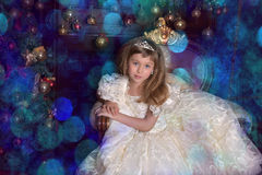 Young princess in a white dress with a tiara on her head at the Christmas tree. At Christmas sitting on the sofa Stock Image