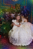 Young princess in a white dress with a tiara on her head at the Christmas tree. At Christmas sitting on the sofa Royalty Free Stock Photography