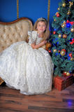 Young princess in a white dress with a tiara on her head at the Christmas tree Stock Images