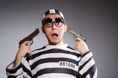 Young prisoner with handgun against gray Royalty Free Stock Images