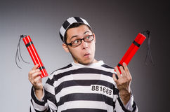 Young prisoner holding dynamite against gray Stock Photography