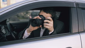 Young private detective man sitting inside car and photographing with dslr camera. Young private detective man sitting inside car and photographing with slr stock video footage