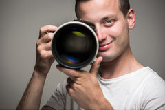 Young pro photographer with digital camera. DSLR and a huge telephoto lens in his well equiped studio, taking photos (color toned image; shallow DOF Stock Photos