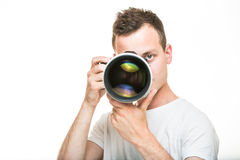 Young pro photographer with digital camera. DSLR and a huge telephoto lens in his well equiped studio, taking photos (color toned image; shallow DOF Royalty Free Stock Photos
