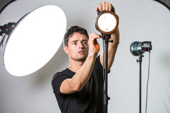 Young, pro photographer setting lights in his studio Stock Image