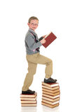 Young prodigy boy on book. Young prodigy boy on stack of books, showing the power of education, knowledge. white background Royalty Free Stock Photos