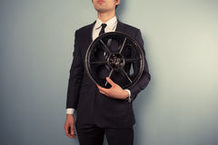 Young producer with film reel. A young movie executive is holding an old film reel Royalty Free Stock Image