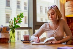 The young producer is sitting in cafe, composing a play, thinking about the nuances, writing thoughts in a notebook. Beautiful blonde woman dressed in a dress royalty free stock photography