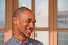 Young Professional African American Man. Close-up profile of a smiling, young, professional African American male standing in front of  windows with blurred Stock Photos