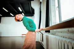 Young professional ballet dancer with hair bun doing arching. Arching near ballet bar. Young professional ballet dancer with hair bun doing arching while royalty free stock images