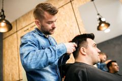 Young professional barber making haircut to customer royalty free stock photography