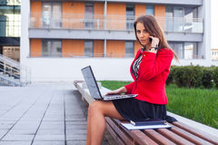 Young professional business woman sitting outdoor with computer. Laptop. In the background office block Royalty Free Stock Image