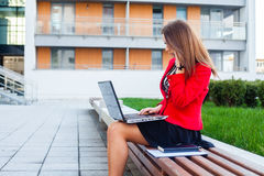 Young professional business woman sitting outdoor with computer. Laptop. In the background office block Royalty Free Stock Photography