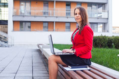 Young professional business woman sitting outdoor with computer Stock Image
