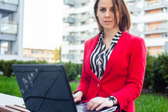 Young professional business woman sitting outdoor with computer Stock Images