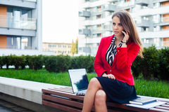 Young professional business woman sitting outdoor with computer. Laptop. In the background office block Stock Image