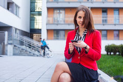 Young professional business woman sitting outdoor with computer. Laptop. In the background office block Stock Photography