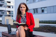 Young professional business woman sitting outdoor with computer. Laptop. In the background office block Royalty Free Stock Images