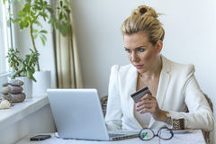 Young professional business woman sitting at table using a laptop computer Royalty Free Stock Image