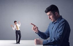 Young businessman fighting with miniature businessman Stock Photography