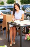 Young professional businesswoman sitting at cafe. Young professional businesswoman sitting at table at cafe royalty free stock images