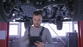 Professional car mechanic inspects automobile on lift during repair and writes notes at service station stock video