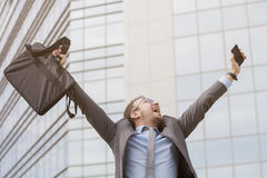Young professional celebrating his success with hands up royalty free stock photos