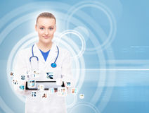 Young, professional and cheerful female doctor. Modern doctor with tablet and many applications on it on blink background royalty free stock image