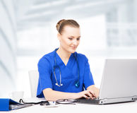 Young, professional and cheerful female doctor working in office Royalty Free Stock Photo