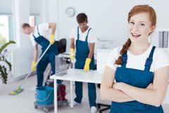 Young professional cleaner. Image of a young professional cleaner standing in light office Stock Photos