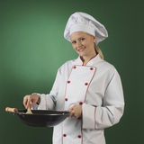 Young professional cook. One atractive cook, she is wearing professional uniform and standing stearing a wok Royalty Free Stock Photos
