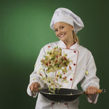 Young professional cook on green background - squa. One atractive cook, she is wearing professional uniform and standing stearing a wok Stock Image
