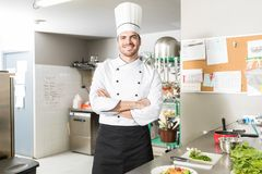 Young Professional Cook Smiling In Restaurant. Good looking Hispanic male chef working in restaurant kitchen stock photo