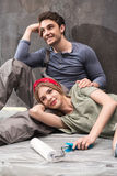Young professional couple resting together on floor during renovation home Stock Photos