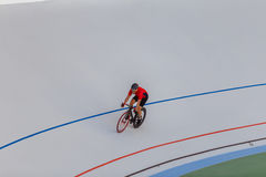 Young professional cyclist on a velodrome. Sports man in a red T-shirt and a black bicycle Royalty Free Stock Photography