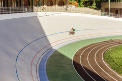 Young professional cyclist on a velodrome. Sports man in a red T-shirt and a black bicycle Stock Images